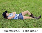 Young teen girl lying in the grass with western style clothing. - stock photo