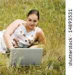 beauty woman with laptop on the green grass - stock photo