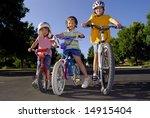 Sisters riding bikes together and laughing - stock photo