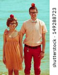 Nerds' honeymoon concept. Portrait of couple of young happy married hipsters in trendy clothes standing together on the beach with apples in their heads. Sunny summer day. Outdoor shot - stock photo