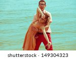 Happy honeymoon concept. Young happy married couple of hipsters in trendy clothes walking and playing on beach. Sunny summer day. Vintage (retro) style. Copy-space. Outdoor shot - stock photo