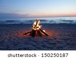 Inviting campfire on the beach during the summer - stock photo
