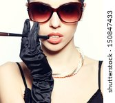 Eyewear concept. Portrait of a fashionable model in vintage sunglasses with a cigarette holder. Perfect skin. Great pearl accessories. Retro style. Close up. Studio shot - stock photo