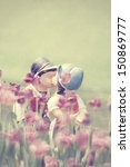 Two kissing vintage dolls in tulip garden. - stock photo