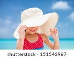 Portrait of cute little girl in a big straw hat at tropical beach - stock photo