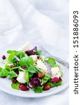 Spinach watercress green mix salad with cranberry, almonds and feta for a gourmet light meal lunch dinner appetiser    - stock photo