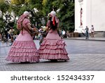 Two old style fashion dressed girls outdoor - stock photo