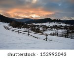 road to the village covered with snow in the mountains under a red winter sunset - stock photo