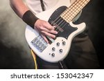 hand of a musician playing a five string bass guitar - stock photo