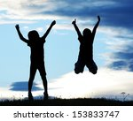 Happy kids silhouettes having fun on meadow at sunset celebrating summer - stock photo