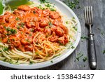 Spaghetti bolognese with shrimp and basil - stock photo