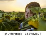 Woman portrait in sunflower field at the sunset - stock photo