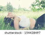 young pregnant woman is resting in the grass - stock photo
