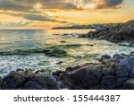 sunrise on the beach, near the small resort village on the edge of the earth. waves breaking on a rocky shore in the sunshine. - stock photo