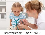 Little girl at the doctor for a checkup - listening to own heartbeat with stethoscope - stock photo