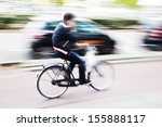cyclist phoning during bicycle ride, shown in motion blur - stock photo