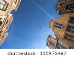 Flying seagull in the sky between old roofs  - stock photo