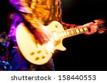 motion blur abstract of a glam rock guitarist wearing glitter clothing - stock photo