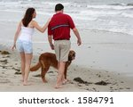 couple with dog at beach - stock photo