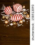 Large Blown Glass Peppermint Candy, Small Christmas Bulbs and snowflakes on a wooden table top - stock photo