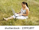 a beauty woman with notebook on the grass - stock photo