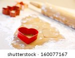 Baking heart shaped gingersnap cookies for Christmas. - stock photo
