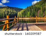 pier on the Lake in mountain near coniferous forest - stock photo