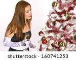 A Hispanic woman in an evening gown and white gloves, holding a glass of champagne, while looking at a decorated Christmas tree. - stock photo