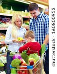 candid portrait of family buying food in supermarket - stock photo