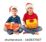 Two smiling kids  in Santa's hat sitting with Christmas gift boxes, isolated on white - stock photo