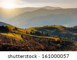 autumn landscape. forest on a hillside covered with red and yellow leaves. over the mountains - stock photo