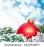 Red christmas ornament ball against blue bokeh background - stock photo