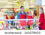 polite grocery staff serves customer in the mall - stock photo