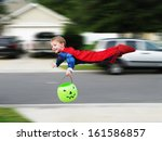 Super toddler. Young toddler flying through the air while trick or treating - stock photo