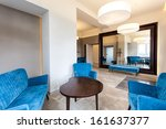 Blue sofa and armchairs in elegant modern interior - stock photo