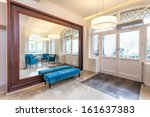 Interior of a hall with mirror and turquoise sofa - stock photo