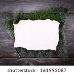 Christmas Fir Tree Border over blank paper on wooden background - stock photo