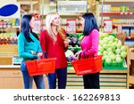 beautiful girls shopping in grocery supermarket - stock photo