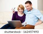 Young couple paying online with credit card - stock photo