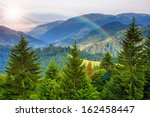 mountain landscape pine trees near valley and colorful forest on hillside under blue sky with clouds and rainbow - stock photo