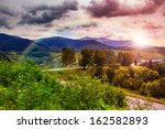 valley near forest on a steep mountain slope after the rain in evening mood - stock photo