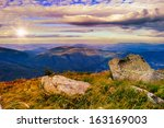 autumn landscape. valley with stones on the hillside. forest on the mountain covered with red and yellow leaves. over the mountains the beam of light falls on a clearing at the top of the hill. - stock photo