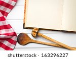 top view of cookbook with kitchenware on white wooden table - stock photo