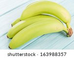 Green Bananas - Unripened bananas on a blue wooden background.  - stock photo