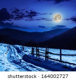 fence by the road to forest in the mountains on a fine winter night - stock photo