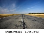 old road between autumn agricultural field with blue sky above - stock photo