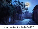 old town curvy cobbled street at night - stock photo