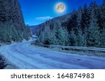 Empty asphalt mountain road near the coniferous forest - stock photo
