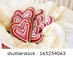 Heart shaped gingerbread cookies decorated in red and gold for Christmas - stock photo