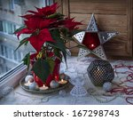 Eve Advent. Christmas star  (Euphorbia pulcherrima) on the window and Christmas decor - stock photo
